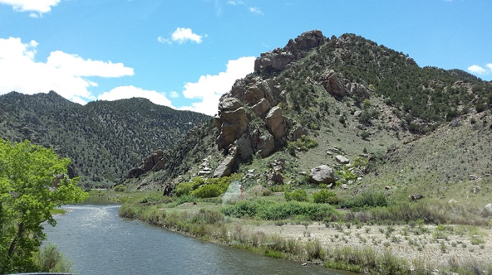 Rocky hill side with river below. Mountain background.